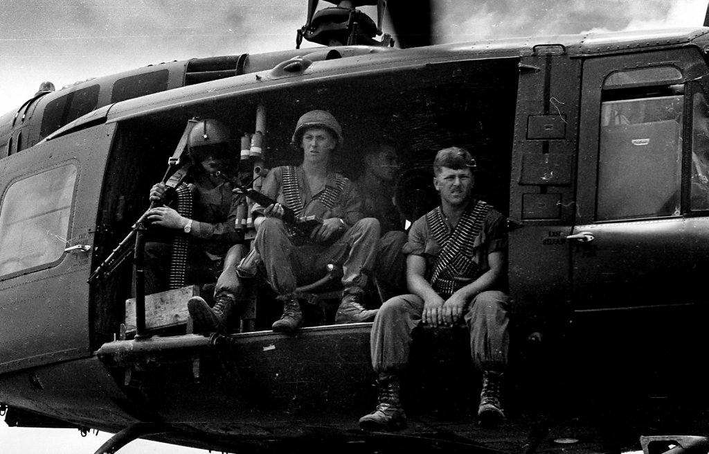 Soldiers sitting at door of  Bell UH-1 Iroquois